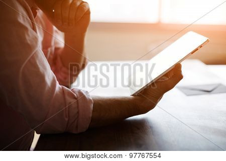 Male person looking to the digital tablet screen while sitting in modern loft interior at the table