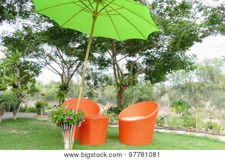 Orange Wicker Style Couch With Green Umbrella In The Garden