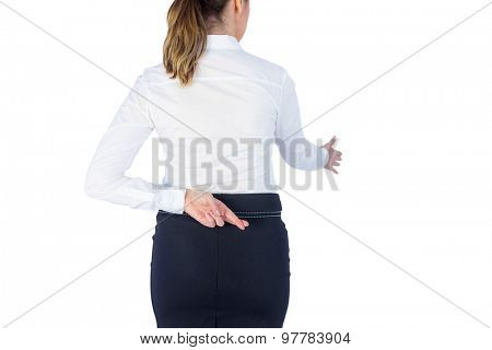 Pretty businesswoman with finger crossed against a white wall