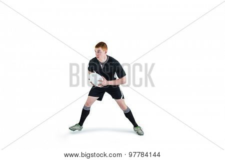 Attentive rugby player running with a rugby ball
