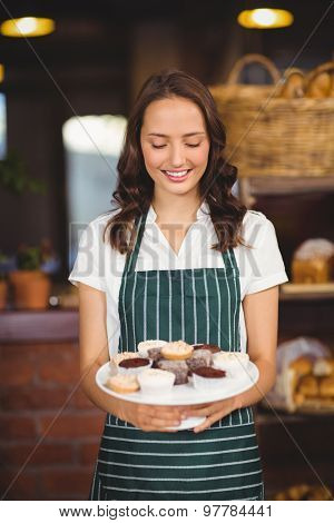 Pretty waitress showing a plate of cupcakes at the coffee shop