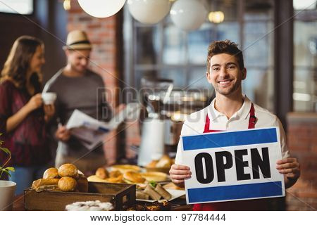 Portrait of a waiter posing with open sign at the coffee shop