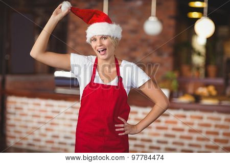 Portrait of waitress touching her santa hat at the coffee shop