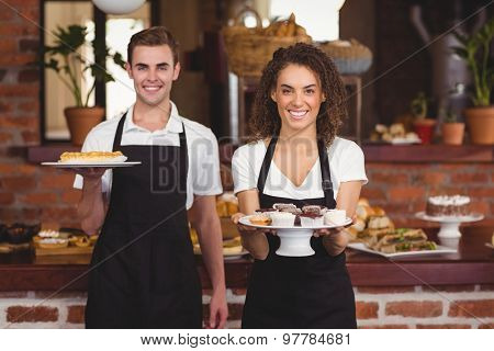 Portrait of smiling waiter and waitress showing plates with treat at coffee shop