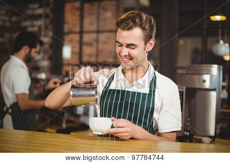 Smiling barista pouring milk in a cup at the coffee shop