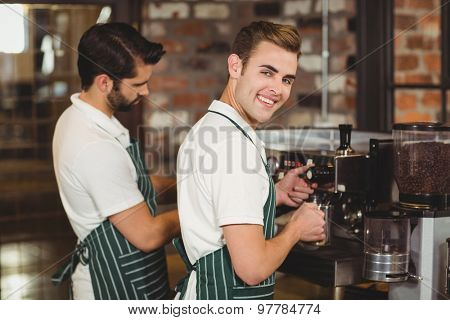 Portrait of two baristas preparing coffee at the coffee shop