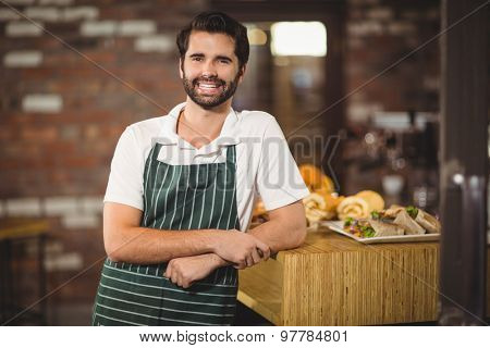 Portrait of a barista leaning on the counter at the coffee shop