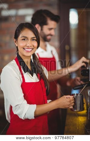 Portrait of a waitress steaming milk at the coffee shop