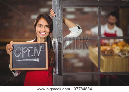 Portrait of waitress showing chalkboard with open sign at coffee shop