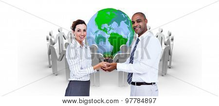 Business colleagues holding plant and looking at camera against human figures surround earth