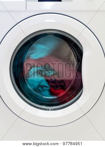 Closeup of washing machine door with spinning laundry