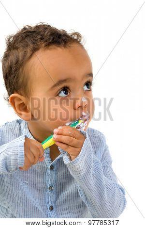 Smiling 18th month old African toddler boy brushing his teeth