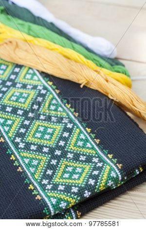 Ukrainian embroidery on the black fabric and thread embroidery on a light wooden table