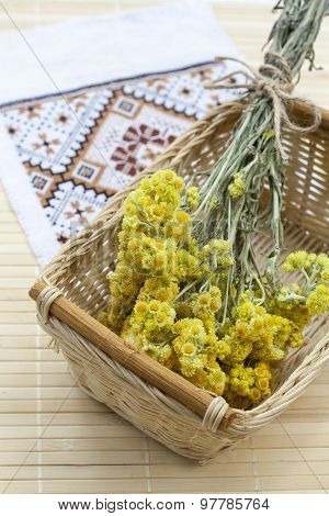 Dwarf everlast flowers bouquet in a wicker basket and napkin with embroidery on light wooden table