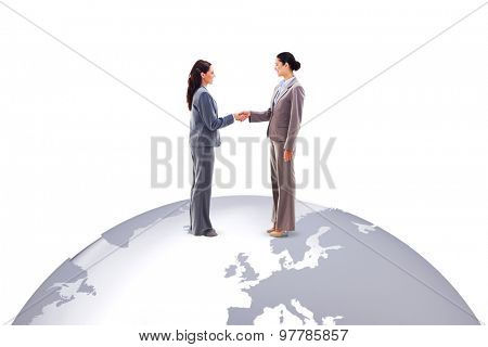 Two businesswomen shaking hands against silver earth