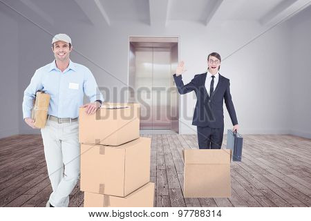 Handsome delivery man leaning on stacked cardboard boxes against room with elevator