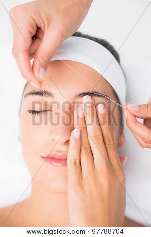 Close up of a hands threading beautiful womans upper eyes