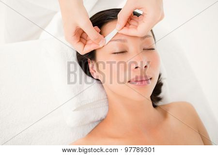 Close up view of hands waxing beautiful womans eyebrow