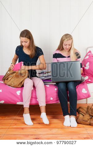two teengirls sitting on bed making homework together with school books and laptop