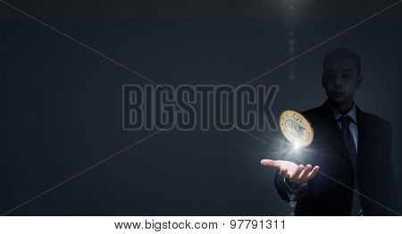 Close up of businessman holding in palms euro coin