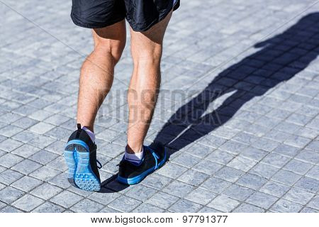 Legs of an athlete running on a sunny day