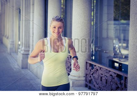A beautiful woman running in the street on a sunny day