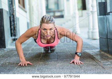 A pretty woman doing push-ups on the floor on a sunny day