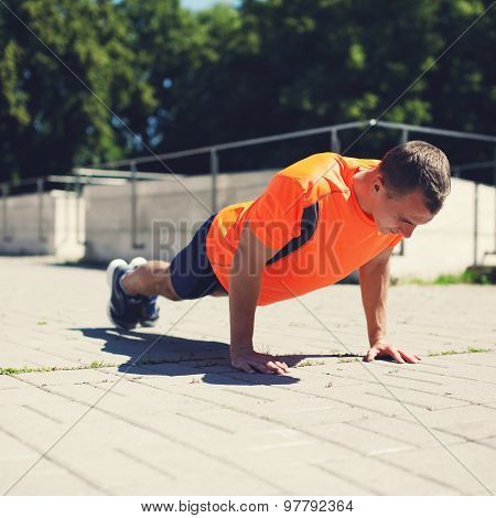 Sport, Fitness And Workout Concept - Sportsman Doing Push-ups Exercise Outdoors In The City