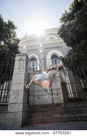 Extreme athlete doing a backflip in front of a building in the city