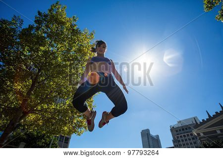 Low angle view of athletic woman jumping in the air in the city