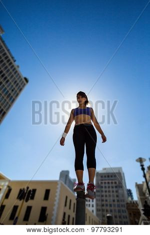 Athletic woman balancing on bollard in the city