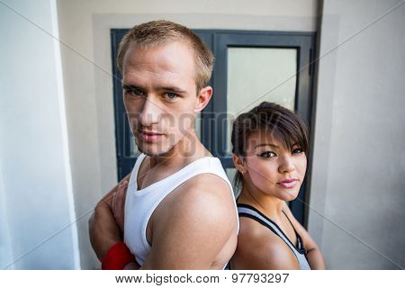Portrait of extreme athletes standing back to back with arms crossed in front of a building