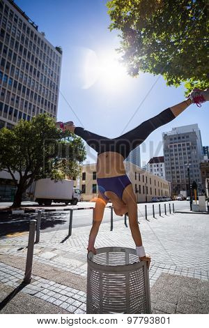 Athletic woman performing handstand and doing split on bin in the city