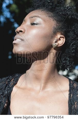 Close up Thoughtful Pretty Young Black Woman with Curly Short Hair, Relaxing with Eyes Closed on a Sunny Day.