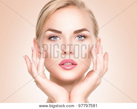 Beauty Woman Portrait. Beautiful Spa Girl Touching her Face. Perfect Fresh Skin. Pure Beauty Model Female looking at camera. Youth and Skin Care Concept.