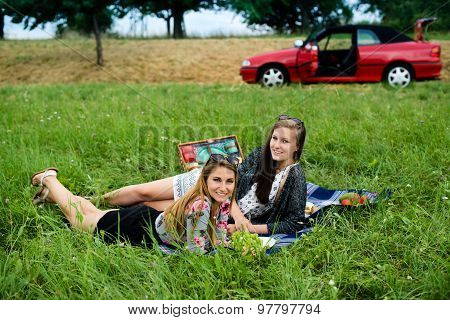 Best friends having a picnic next to their car