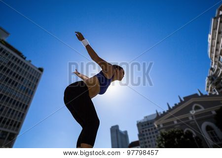Athletic woman preparing for jump in the city