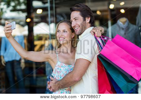 Smiling couple embracing and taking selfies at shopping mall