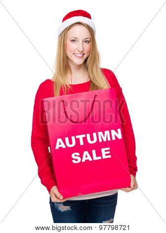 Woman with paper bag showing autumn sale