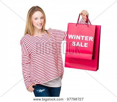 Woman holding with shopping bag and showing winter sale