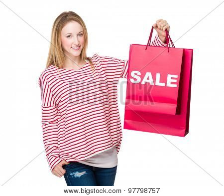 Woman holding with shopping bag and showing sale