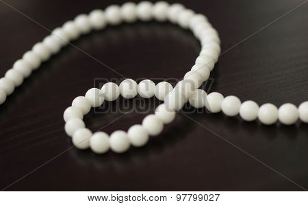 Necklace From Stone White Beads On A Dark Surface Close Up