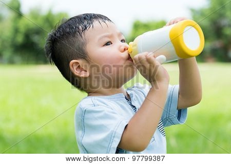 Little boy feeling thirsty and drink with water bottle