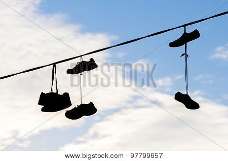 Silhouettes Of Shoes Hanging On Cable Against Sky.