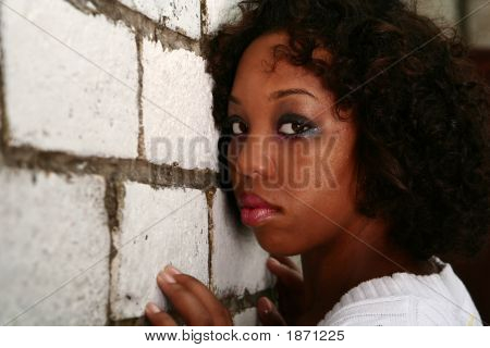 African American Girl Lean Her Face On Brick Wall