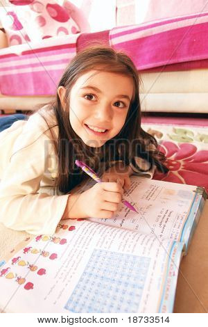 Girl studies math on carpet