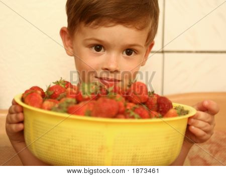 The Child Looks At A Plate With Red Berries