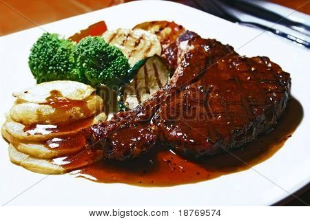 grilled t-bone steak with sauce and grilled vegetables