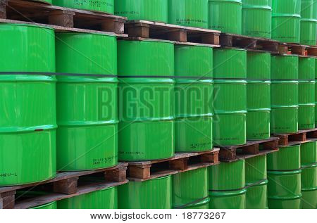 Assembly of green oil drums on wooden pallets