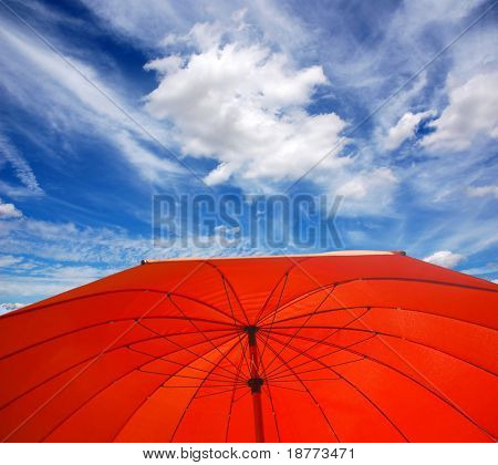 Red sunshade umbrella with blue sky